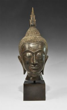 18th-19th century AD. A cast head of the Buddha with angular features, eyelids closed, elongated earlobes with slots, pelletted cap with conical upper and five-pointed ushnisa, symbol of ultimate wisdom; mounted on a custom-made stand.