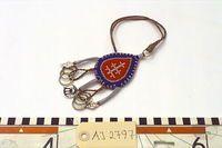 Renlycka, amulett som hängs i kvinnans bälte. Från Ammarnäs - Tärnaby området. Droppformad klädesdyna som är tennbroderad. Ena sidan är blå i mitten med rött kläde i sidorna, den andra sidan är röd i mitten och blå i sidorna. Tenntråden är både plattdragen och vanlig rund tvinnad. Från nedre delen av amuletten hänger 3 tenntrådsbeklädda armar ut. I ändana i dessa är ett silverlöv hängt i 2 av dem och en malja i den 3:e. 2 tvinnade skinnsnoddar hänger ner med 3 mässingsringar i ändana. ...