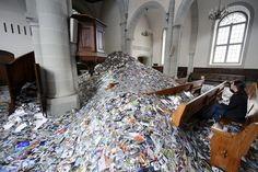 A woman observes the art installation '24 hours in photos' by Dutch photographer Erick Kessels, containing 350,000 photos sized 10x15cm and piled up in Sainte Claire church during the 'Festival Image' in Vevey, Switzerland, 10 September 2014. The festival with 68 projects and over 1,500 photographs runs from 13 September to 05 October. (EPA/LAURENT GILLIERON)