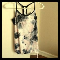 NWOT Workout tank with built in bra This pink and gray flowered top has a built in bra, and has an adjustable tie at the bottom. It's made from polyester and elastane with a mesh backing to keep you cool during your workout. Brand new and has never been worn. fabletics Tops Tank Tops