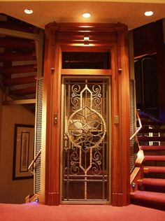 Beautiful home elevator door. Not sure if I like the stairs wrapped around it. To tuck away or focus on the elevator...