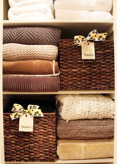 Baskets placed next to stacks of blankets help keep stacks from falling over & keep sheet sets together