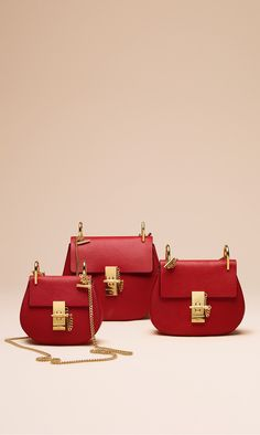 Stand out this season with the boldly festive Drew in plaid red with glittering gold hardware