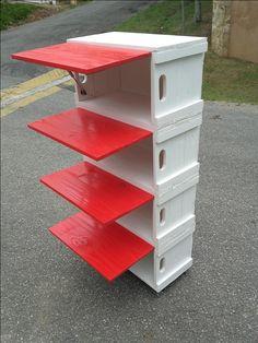 Estante com 4 caixotes pintados em branco. E as portas pintadas em vermelho. E embaixo, rodízios.