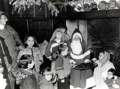 """""""Ho, ho, ho."""" Christmas festivities for visitors at the Welsh Folk Museum, St Fagans in December 1989, Santa with some of the young visitors, as they sample traditional treacle toffee"""