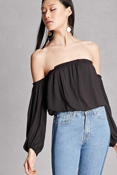 A woven top by Lush™ featuring a ruffled off-the-shoulder neckline, long sleeves with button cuffs, and an elasticized waist.