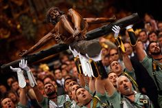 Spanish legionnaires sing an anthem as they carry a statue of the Christ of Mena during Holy Week