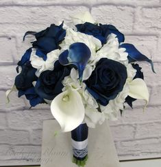 A navy and white wedding bouquet of class and elegance. The real touch calla lilies are soft to touch and look so real, you are sure to love them. Bouquet is designed with 10 navy and white calla lilies, creamy white hydrangea, white stephanotis, with blue roses, framed with hydrangea leaves. Handle treatment is wrapped with navy and white satin ribbon, white lace sash for an added elegant detail. Bouquet measures 10 ( 25 cm ) wide x 12 ( 30 cm ) tall.  Coordinating bridesmaid bouquet…
