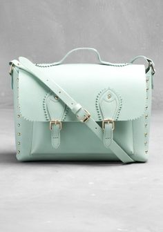 Leather shoulder bag | Mint | & Other Stories. £95. & OTHER STORIES Made from smooth, chunky leather, this satchel-style bag features a foldover design with a grab handle and shoulder strap. Details include gold studs, serrated edges, an unlined interior and hidden magnetic snaps on the front pocket.