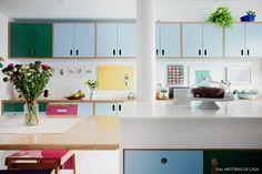 Cozinha colorida com armários de compensado naval revestido com fórmica nos tons azul e verde.