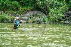Fisherman catching fish in a rushing river