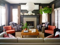 Dark living room with fig, white light fixture, brass and orange accents, and tan curtains (via desire to inspire)