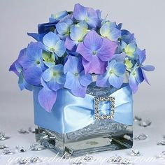 Blue hydrangea wedding centerpiece decorated with satin ribbon and a rhinestone buckle - via www.yourweddingcompany.com