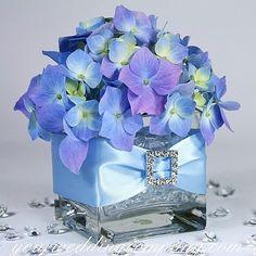 Blue hydrangea wedding centerpiece decorated with satin ribbon and a rhinestone buckle - via www.yourweddingcompany.com
