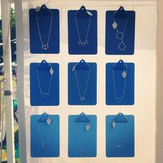 a brilliant outdoor craft show display idea by freshie and zero jewelry...love the clipboards and varying shades of blue.  what a great way to keep things in place during windy, outdoor shows.  and a great idea for tighter booth displays where you need to maximize booth space and build UP!