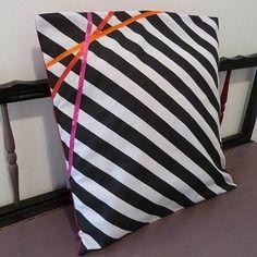 Housse de coussin graphique rayée noir et blanc et rubans croisés rouge, rose, orange