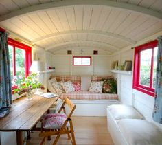 Shepherd's Hut, Butley on Best of Suffolk.  Interior.  Like the cosy feel of the cabin roof and contrast frame colour.  Lots of cushions.