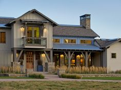 Stone garden beds planted with ornamental grasses lend golden color to the front yard of this rustic home.