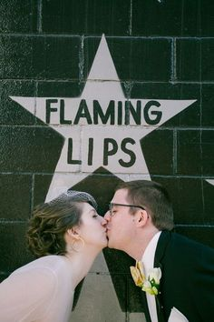 Couple kissing in front of Flaming Lips star @myweddingdotcom