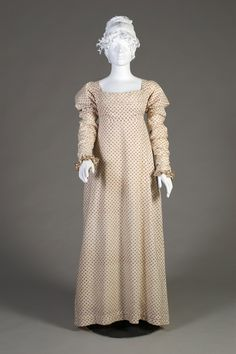 White cotton day dress printed with red and blue floral rondels overall. The dress with scoop neck and high waist. A panel from the waistband flaps up over the bust, ties at the waist are pulled to the tightly pleated back. The short sleeves with sewn in fitted undersleeve with ruffled wrist.  English, ca. 1808-12  Silverman/Rodgers Collection, KSUM 1983.1.28