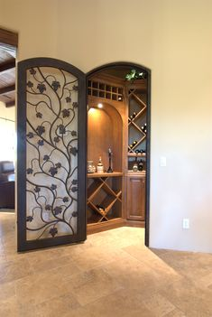 Walk-in wine closet with individual and bulk storage.  This door is a wrought iron door with grape motifs fitting for the use as a wine closet door.