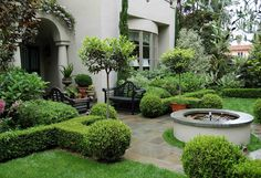 small-front-yard-design-with garden-bench-potted-plants-arched-entryway