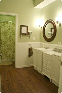 darker floors with darker mirrors  stainless steel faucets and fancy knobs   light neutral wall