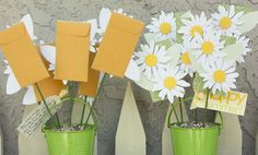 This cute bucket of paper daisies is in fact a Gift Card Bouquet.  The little brown envelopes are covered with a pretty green paper with the paper daisies attached to each one (You could use silk flowers)