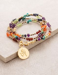 An intricate arrangement of gemstones and seed beads create a stunning double wrap bracelet using the colors of the chakra to create a perfect balance of style
