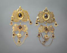Paar 14 karaat gouden 'spiegelbellen'. Deze hangers zijn gedragen door een vrouw op Tholen, omstreeks 1860-1870. Spiegelbellen zijn typisch Thools. Deze exemplaren zijn echter bijzonder, vanwege de toevoeging van granaat en bloedkoraal. #Tholen #Zeeland