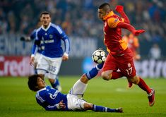 Atsuto Uchida of Schalke challenges Burak Yilmaz of Galatasaray during the UEFA Champions League round of 16 second leg match between Schalke 04 and Galatasaray AS at Veltins-Arena on March 12, 2013 in Gelsenkirchen, Germany.