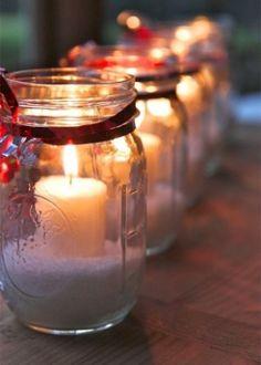 Potes de vidro descartados podem se transformar, em poucos passos, em castiçais para a mesa de Natal. Basta preencher um terço do recipiente com sal grosso e apoiar nessa base, as velas do tipo recháud. Por fim, use um fitilho vermelho para arrematar o delicado ao enfeite.