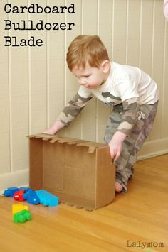 """Your preschoolers and toddlers will love this quick and easy cardboard crafts tutorial to turn a cardboard box into a DIY bulldozer blade toy for kids. Use up those extra Amazon boxes and make something awesome (and free!) for the kids. They'll love using the DIY bulldozer toy to scoop up LEGOs or other small toys. You can make """"rocks"""" out of the packing paper! #DIY #activities #kids #indoorplay #playideas"""