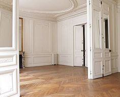 traditional french apartment dining room. all white, herringbone floors