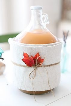 Dress up an apple juice jug with linen towels, twine and a pressed maple leaf! Dreamy Whites: A Fall Table and a winner~