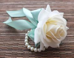 Do people do wrist corsages or pin-on corsages for the moms and grandmas? This could be pretty with some white spray around a blush flower.