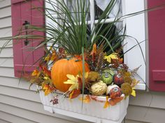 I love my fall window boxes.  A combination of artificial and real items.  The pumpkin is a fake Jack-O-Lantern that will be turned around and plugged in for Halloween.  There are mini lights woven through, so they are also beautiful at night.