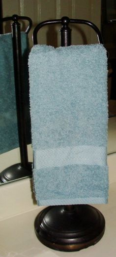 Repurposing: A toilet paper stand to hold a regular size hand towel on the vanity.