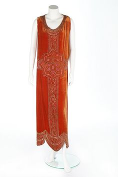 An embroidered brick-red velvet evening dress, probably Callot Soeurs, early 1920s. An embroidered brick-red velvet evening dress, probably Callot Soeurs, early 1920s. embroidered with gold running stitches and pink floss silk, spangled with pink bugle beads with orientalist motifs, large central medallion, scalloped hem embroidered to shape, lined in chiffon, bust approx 86-92cm, 34-36in. - See more at: http://kerrytaylorauctions.com/one-item/?id=62&sub=%20&auctionid=429#.dpuf