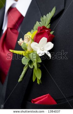red tie and three-piece black suit for groomsmen, with red and green boutonnieres