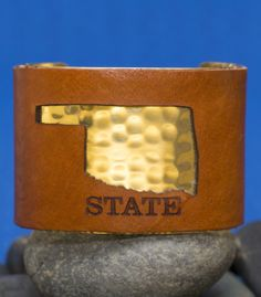 2 inch Oklahoma State cutout on brown leather overlaid on signature silver or gold metal Rustic Cuff. Adjustable to fit most wrists.