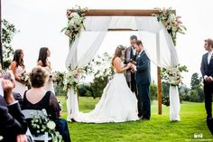 San Diego wedding at lomas santa fe country club bride strapless tulle ball gown with beaded bodice and purple sash with groom navy blue suit with matching vest and white dress shirt with white bow tie and white floral boutonniere exchanging rings during ceremony
