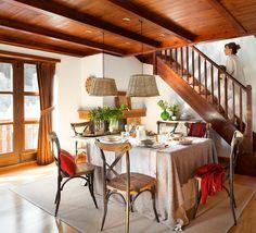 Comedor con sillas de respaldo cruceta y lámparas de mimbre junto a escalera de madera