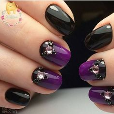 Purple and black nail design with rhinestones.