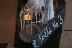 Slate base. Table no. 3 on slate. Milk glass vases. Votive candles. Mini bird cage. Thought the bird cage could be filled with a mini arrangement or simple with babies breath. https://www.facebook.com/focalpointdesignsanddecor