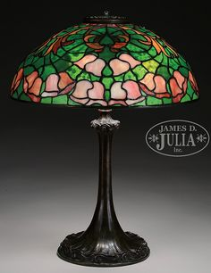 "Tiffany Studios leaded table lamp has pink and red bellflowers set against a heavily mottled green background. Top of the shade has red and orange stylized leaves against the same heavily mottled background. Stylized leaves show wonderful sparkle and fire when lit. Signed on inside rim ""Tiffany Studios New York"". Shade rests on a Tiffany Studios bronze base with wave design encircling the foot and again at top of stem. Base is complete with 3 socket cluster and replacement heat cap, all…"