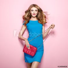 Blonde young woman in elegant blue dress. Girl posing on a pink background. Jewelry and hairstyle. Girl with handbag. Fashion photo
