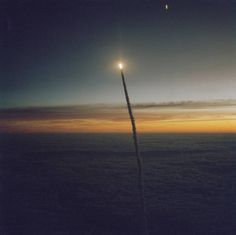 Shuttle Challenger flies above the clouds during a dawn launch, photographed from the air by a Shuttle training aircraft