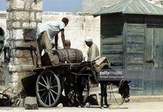 Libyanese men wearing regional clothes load a cart with barrels in Benghazi, Libya.