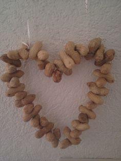 Hart van pinda's. Rijg ijzerdraad door pinda's en zo kan je het in vorm buigen. Staat leuk in de tuin!